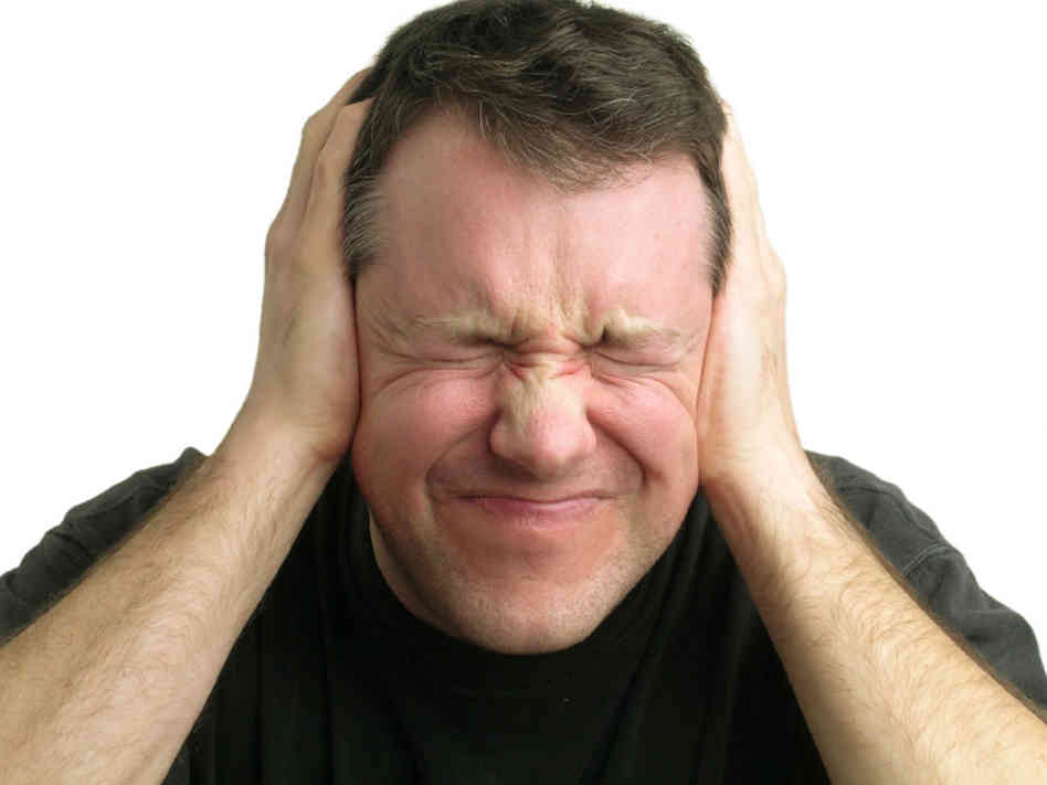 Middle-aged man annoyed or in pain with his hands over his ears and his eyes shut.